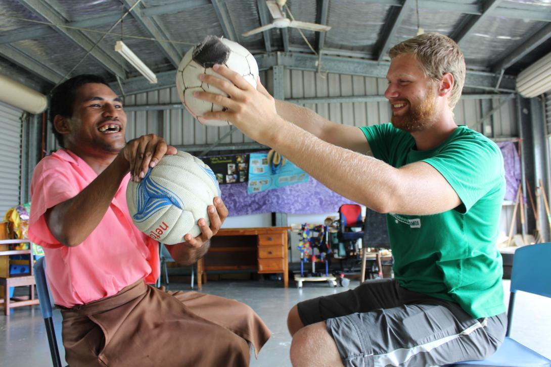 A care volunteer making a disabled man smile playing ball games